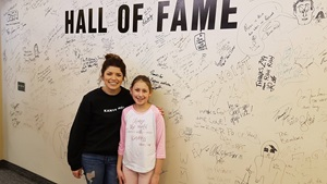 Girl with radio DJ in front of wall of signatures