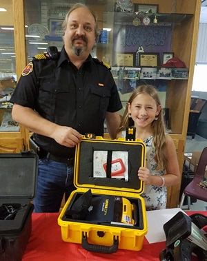 Girl and firefighter with defibrillator