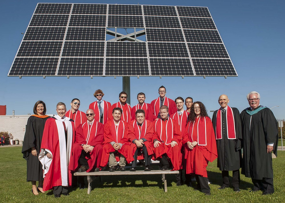 College grads and a solar panel