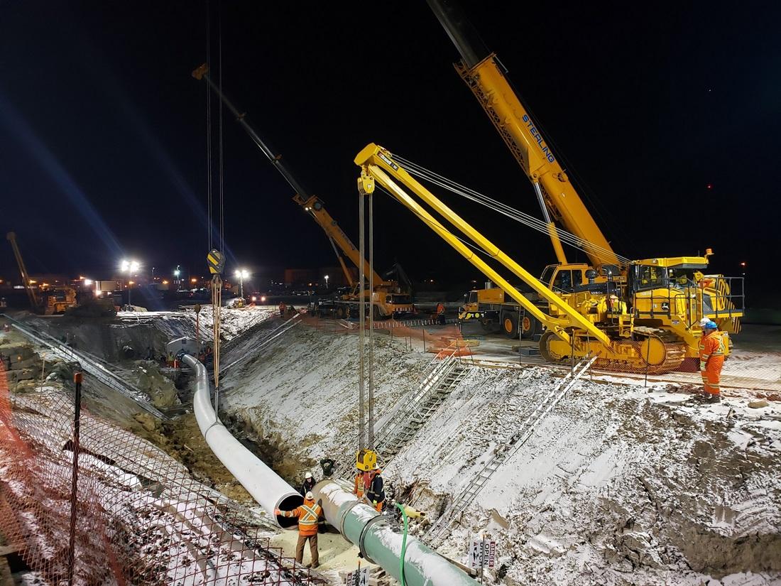 Cranes lowering pipe into trench