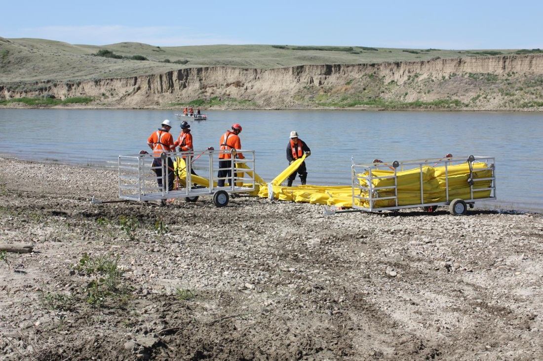 workers deploying containment boom during a drill