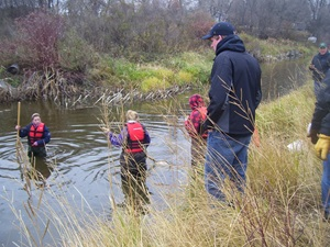 students collecting water samples in a marsh