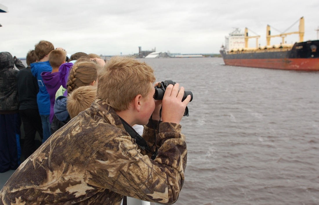 Student looking across river with binoculars